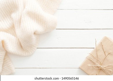 Autumn composition. Feminine desk table with knitted scarf and gift box on wooden white background. Flat lay, top view. Nordic, hygge, cozy home concept