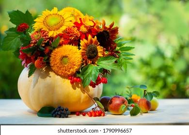 Herbstzusammensetzung mit Blumen auf Kürbis auf Holzhintergrund, im Freien