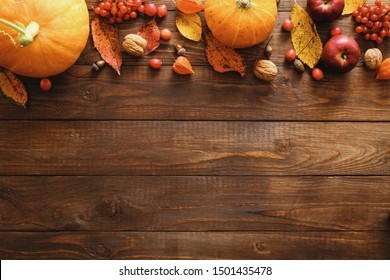 Autumn composition. Frame border made of pumpkins, fallen leaves, apples, red berries, walnuts on wooden background. Happy Thanksgiving concept. Flat lay, top view, copy space