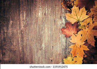 Autumn composition. Frame made of autumn dried leaves on dark wooden vintage background. Autumn, fall, background. Flat lay, top view, copy space