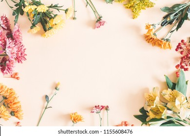 Autumn composition. Frame made of fresh flowers on pastel beige background. Autumn, fall concept. Flat lay, top view, copy space