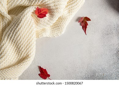 Autumn composition. Frame made of knitted plaid or scarf, fallen leaves on pastel grey background. Autumn, fall concept. Flat lay, top view, copy space.
