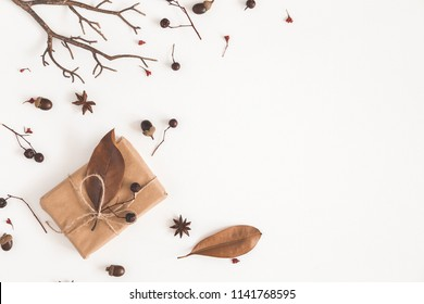 Autumn composition. Gift box, dried flowers and leaves on white background. Autumn, fall concept. Flat lay, top view, copy space