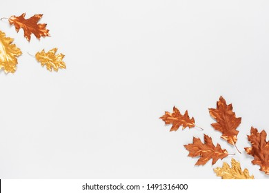 Autumn composition with a gold and copper spray painted natural leaves on white background. Flat lay, top view, copy space. Minimal concept