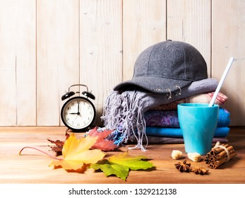 Autumn composition. Gray cap, several knitting scarves, cup of tea and leaves on wooden table. Space for text