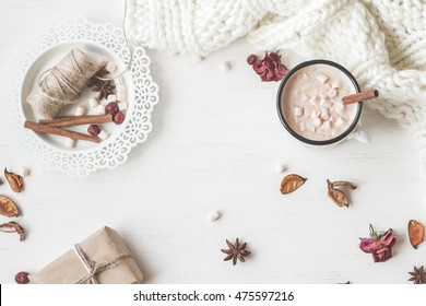 Autumn composition. Hot chocolate, knitted blanket, gift, dried flowers and autumn leaves. Flat lay, top view