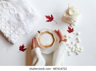 Autumn composition. Hot chocolate, knitted blanket, lit candle, autumn leaves. Flat lay, top view, white background. Hands holding cup of warm drink