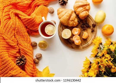 Autumn composition. Hot tea with lemon, croissants on wooden tray,  autumn leaves, yellow flowers on white background.  Cozy orange sweater. Flat lay, top view.