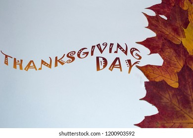 Autumn composition. Inscription, word Day Thanksgiving. Bright maple edge and copy space. Autumn concept.
