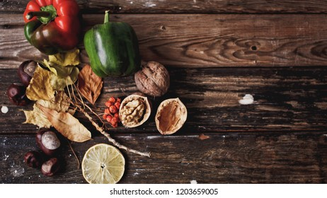 Autumn composition. Pattern made of leaves, flowers, tomatoes, nuts, pepper, pumpkin, berries on wooden background. Autumn, fall concept. Flat lay, top view