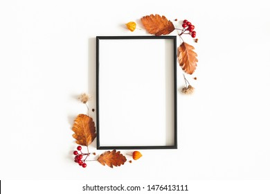 Autumn composition. Photo frame, flowers, leaves on white background. Autumn, fall, thanksgiving day concept. Flat lay, top view, copy space