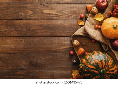 Autumn composition. Pumpkins, blanket, fallen leaves, apples, red berries, walnuts on wooden table. Happy Thanksgiving concept. Flat lay, top view, copy space