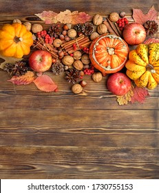 autumn composition with pumpkins, cones, berries, apples, nuts, cinnamon on wooden table background. copy space