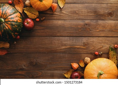 Autumn composition. Pumpkins, dried fall leaves, apples, red berries, walnuts, on wooden table. Happy Thanksgiving concept. Flat lay, top view, copy space