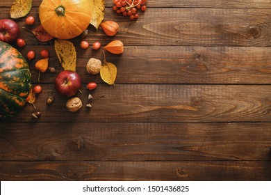 Autumn composition. Pumpkins, fallen leaves, apples, red berries, walnuts on wooden table. Happy Thanksgiving concept. Flat lay, top view, copy space