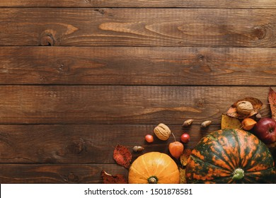 Autumn composition. Pumpkins, fallen leaves, acorns, red berries, walnuts on wooden table. Happy Thanksgiving concept. Flat lay, top view, copy space