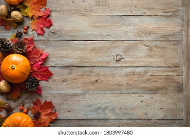 Autumn composition - Pumpkins,  maple leaves, pine cones  on wooden background, creative flat lay, top view, copy space. Seasonal autumn holiday concept. - Shutterstock ID 1803997480