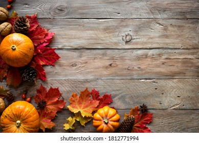 Autumn composition - pumpkins, autumn maple leaves, pine cones  on wooden background, creative flat lay, top view, copy space. Seasonal autumn Thanksgiving holiday concept. - Shutterstock ID 1812771994