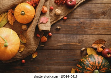 Autumn composition. Pumpkins, sackcloth, fallen leaves, apples, red berries, walnuts on wooden table. Happy Thanksgiving concept. Flat lay, top view, copy space