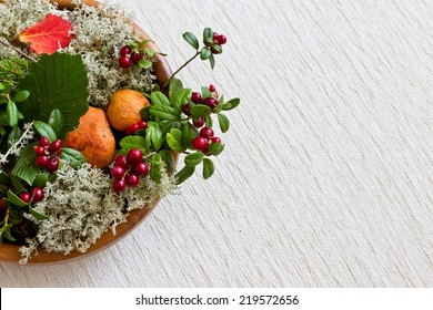 Autumn composition: red cep mushrooms with white moss, pine branch, colorful leaves, cranberries in wooden bowl at white linen background close up