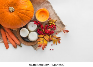 Autumn composition of rowan berries, pumpkins, candles and colorful leaves on the cloth of burlap on white background
