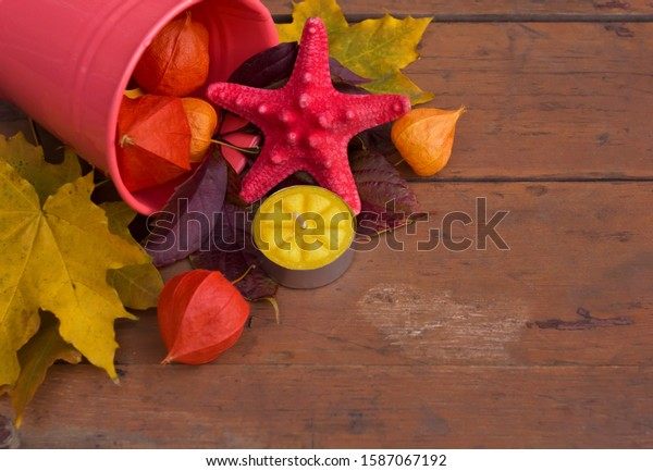 Autumn composition with a starfish, candle, fizalis and yellow leaves on an old shabby wooden background. Daytime garden scene with autumn gifts.