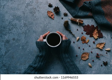 Autumn composition. Woman's hands with cup of coffee, warm blanket, autumn leaves, cinnamon sticks on vintage gray background. Hot drink for autumn cold days. Cozy concept, autumn mood. Toned image.
