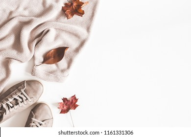 Autumn composition. Women fashion clothes on white background. Sweater, sneakers, dried leaves. Autumn, fall concept. Flat lay, top view, copy space