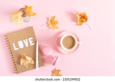 Autumn composition. Women's office desk. Dried leaves, notebook, cup of coffee, macaroon on pastel pink background. Fall concept. Autumn background. Flat lay, top view, copy space