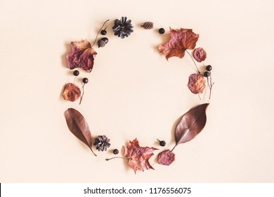 Autumn composition. Wreath made of dried leaves on pastel beige background. Autumn, fall concept. Flat lay, top view, copy space