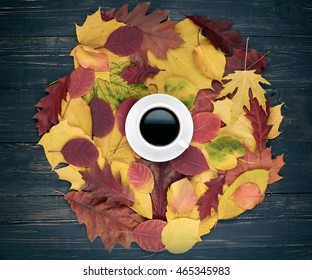 Autumn concept. Cup of coffee and autumn leaves over dark wooden background