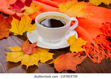 Autumn concept. A cup of coffee in yellow leaves