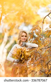 Autumn concept. Happy blond woman looking at the camera and holding a bouquet from maple leaves in front of her.