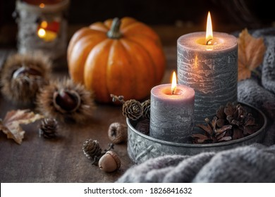 Autumn concept or Thanksgiving celebration concept with two lit candles, orange pumpkin at the background, chestnuts and pine cones