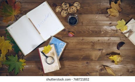 Autumn concept top view. Books, maple leaves, tea on the old wooden table. Woman writing notes in the notebook