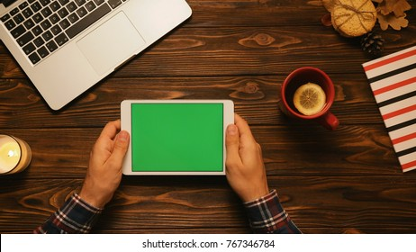 Autumn concept. Top view of male hands holding tablet computer with green screen on the old wooden table. Chroma key