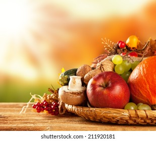 Autumn concept of traditional food. Mix of pumpkins, fruit and vegetable on wooden table with blur background. Free space for text