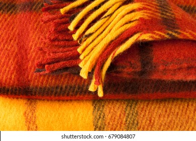 Autumn concept. Wool checkered Blanket. Plaid. Tartan rug. Yellow, red-brown background.