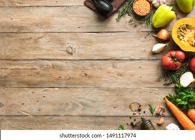 Autumn cooking background with seasonal organic vegetables on wooden table, top view, copy space. Ingredients for autum seasonal soups and dishes.