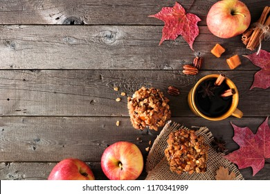 Autumn corner border with apple caramel muffins and hot drink. Top view table scene on a rustic wood background. Copy space.