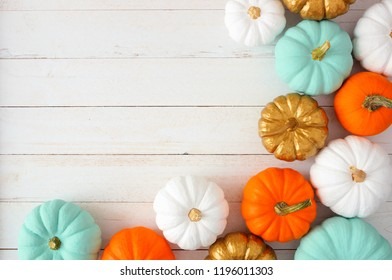 Autumn corner border of various colorful pumpkins on a white wood background. Top view with copy space.
