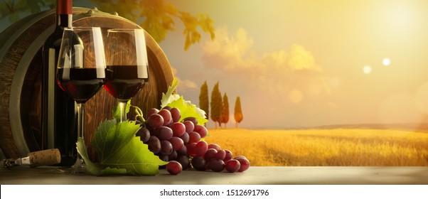 autumn countryside wine background; vine, red wine bottles, wineglass, wine barrel; wine tasting concept