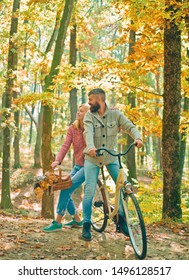 Autumn couple. Bearded man and woman relaxing in autumn forest. Romantic couple on date. Date and love. Autumn date hike in forest. Couple in love ride bicycle together in forest park.