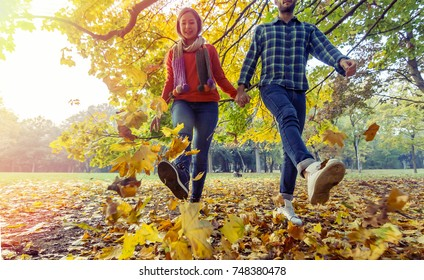 autumn couple in love walking together hand in hand on colorful fallen brownish orange leaves of nature park.