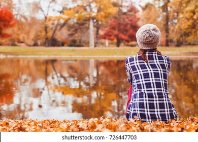 autumn cozy background, beautiful woman sitting near the lake in fall season