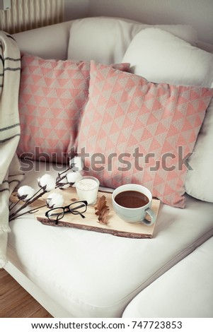 Autumn cozy breakfast. Romantic breakfast. Cotton, a cup of hot coffee, a candle, a plaid, glasses. Autumn cosiness. A tray with breakfast is on the couch. A cozy winter evening.