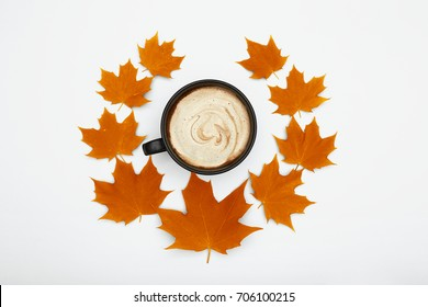 Autumn cozy coffee surrounded with maple leaves, top view, flat lay