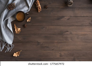 Autumn cozy composition with gray soft plaid and cup of coffee. Seasonal autumnal coziness with warm blanket, coffee, leaves and cones. Cozy home and hygge concept on wooden background, copy space.