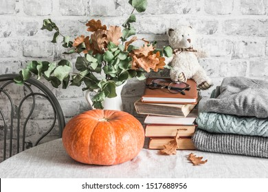 Autumn cozy home still life. Pumpkin, dry branch pitcher, stack of books, pile of winter autumn sweaters,  teddy bear on the kitchen table. Flat lay