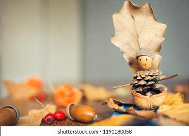 autumn craft with kids. children's cute boat with man made of natural materials.